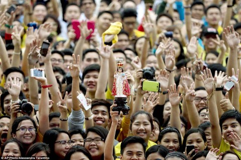 »Infant of Prague« is held up by a devotee as the crowd waits for Pope Francis to arrive at Santo Tomas University, 2015, photo: dailymail.co.uk