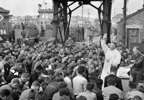 June 6, 1944, Catholic chaplain conducts services on a pier for the first D-Day assault troops in Weymouth, England