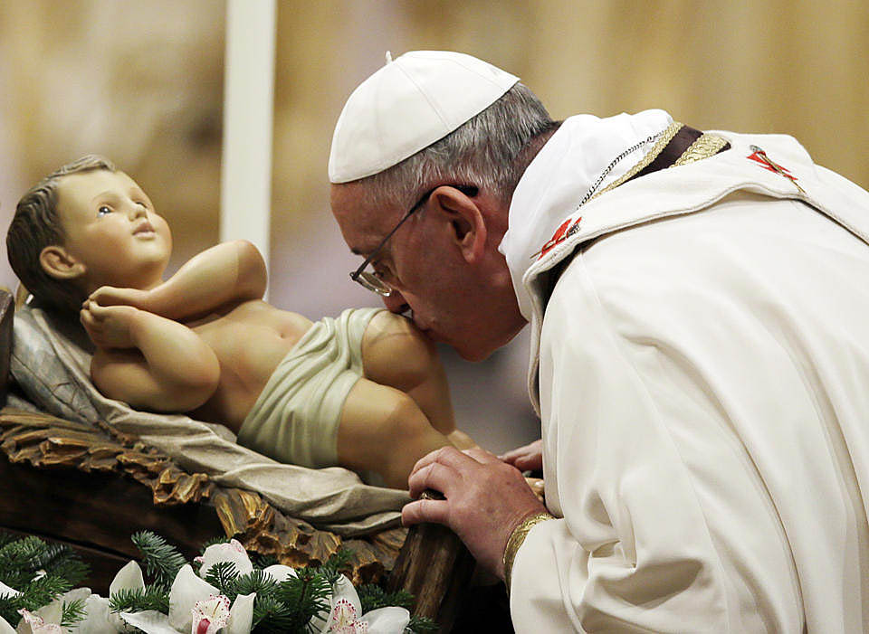 Pope Francis kisses a statue of Baby Jesus as he celebrates Mass on the feast of the Epiphany in St Peter's Basilica at the Vatican 2014