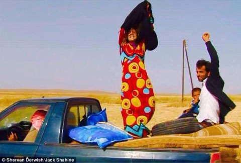 Syrian woman tears off her shapeless islamic black robe as she enters Kurdish-controlled territory