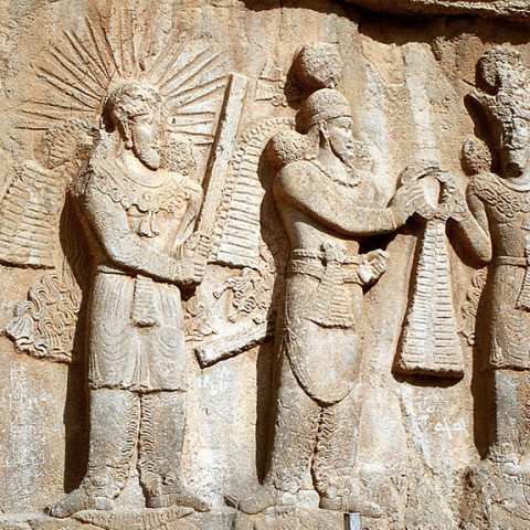 Mithra on the left: Investiture of Sassanid emperor Ardashir I or II (3rd century CE bas-relief at Taq-e Bostan, Iran. On the left stands the yazata Mithra with raised barsom, sanctifying the investiture.