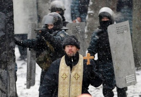 Ukrainian Greek Catholic Church priest prays as he stands before pro-European Union activists during clashes in central Kiev, Ukraine