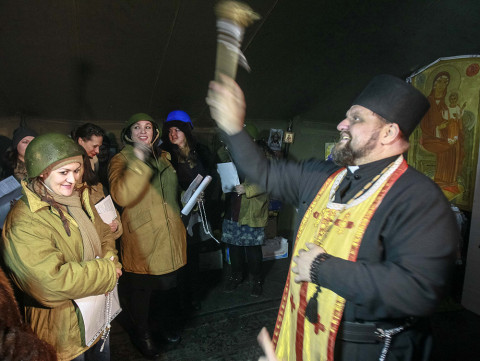 Ukrajinský katolický mejdan: A priest blesses anti-government activists, who formed a women's self-defence unit, inside a makeshift tent chapel at Independence Square in Kiev February 10, 2014. Photo: REUTERS/Gleb Garanich