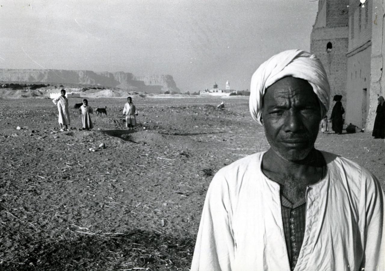 Objevitel fantastického pokladu Muhammad Ali Khalifah al-Samman stojí ve vesnici al-Qasr. V pozadí vpravo Deir Anba-Balamūn (klášter sv. Palamon) a Jabal al-Tarif je na levé straně.